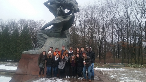 a group of students standing under the Frederic Chopin monument in Poland