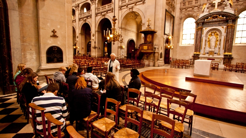 Students on a tour of the Marais (a district in Paris) sit inside Saint-Paul Saint-Louis Cathedral and learn about the history of the area and church